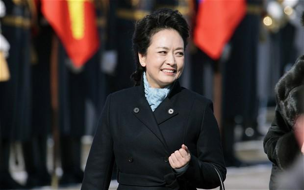 Peng Liyuan simply dressed in a black coat and light blue scarf