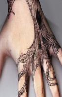 Gnarly tree tattoo on someones hand.