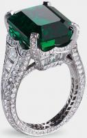 Centered by a 13.73 carat emerald and featuring 14 baguette diamonds a