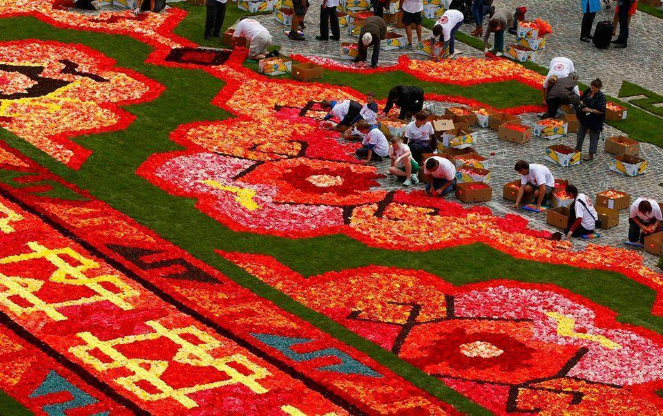 Gardeners work on the design of a giant flower carpet at Brussels' Gr