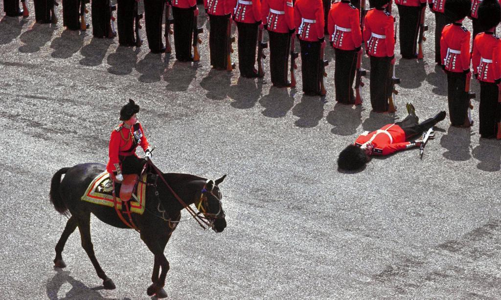 A foot guard passes out as Queen Elizabeth II rides past during the tr