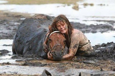 This horse got stuck in the mud. The woman had been holding it's head